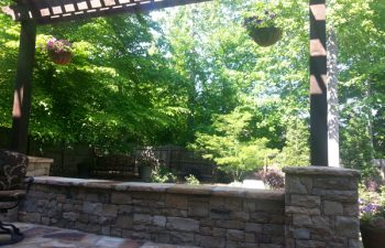 a flagstone porch with a stone wall and wooden pergola