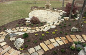 garden flagstone paver leading to a flagstone patio with an outdoor stone fireplace