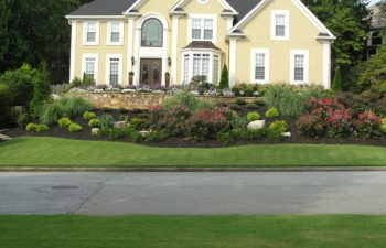 a manicured lawn and well-cared plants in front of a house