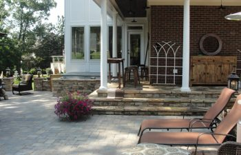 a house with a flagstone porch and paver patio