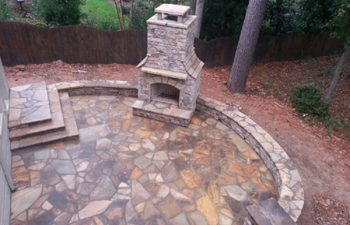 a flagstone patio with an outdoor stone fireplace