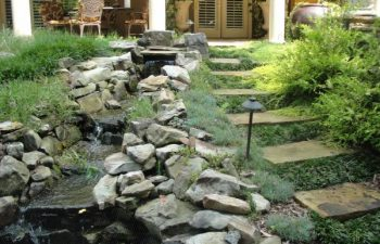 a flagstone paver next to the garden stream with designed hardscape
