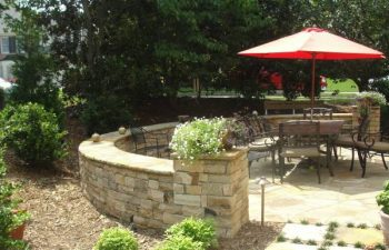 a flagstone patio with retaining walls in the backyard