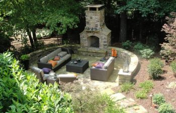a backyard flagstone patio with an outdoor stone fireplace