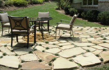 a flagstone patio with a table and four chairs